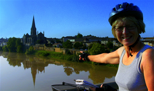 Female cyclist pointing to church spire on Bordeaux to Beziers tour