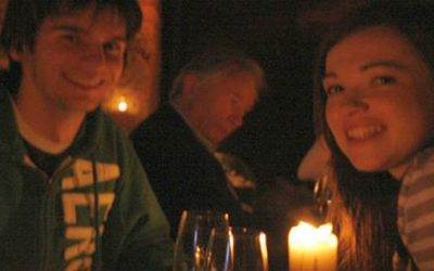 3 youth smiling over 2 glasses of wine and a candle in a dimly lit room