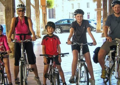 Family Mum Dad 3 children wearing cycling helmets on bikes in Bordeaux